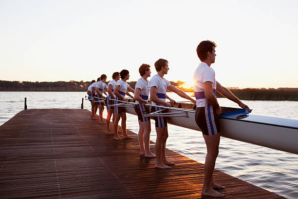 Side view of men holding boat stock photo