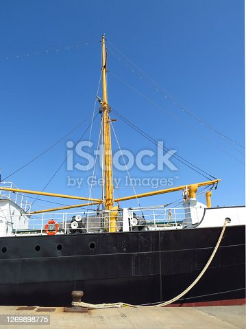 Side view of merchant ship hull and its rigging moored at industrial dock under intense blue sky. Maritime navigation and transport.