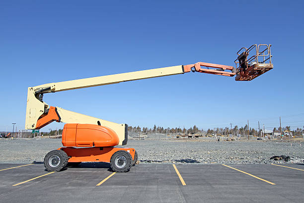 Side View Of Mobile Work Platform On A Construction Site Mobile boom lift equipped with a work platform, commonly seen on construction sites and for building maintenance. mobile crane stock pictures, royalty-free photos & images