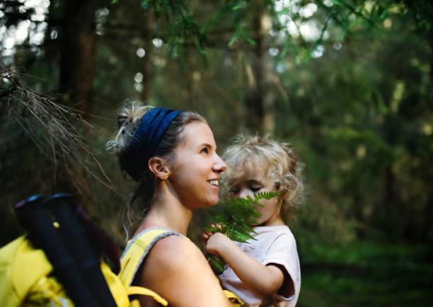 vista laterale della madre con piccola figlia all'aperto nella natura estiva, a riposo. - forest bathing foto e immagini stock