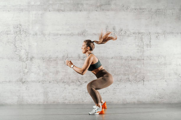 side view of muscular focused brunette with ponytail and in sportswear jumping in front of brick wall in gym. - training imagens e fotografias de stock