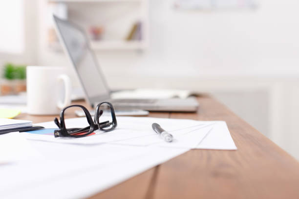 seitenansicht der schreibtisch mit brille, laptop und andere gegenstände - schreibtischunterlagen stock-fotos und bilder