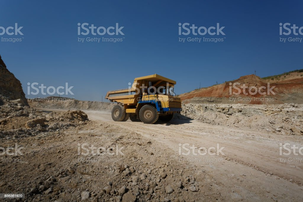 Side view of one yellow tip truck with a shadow on a natural background. Huge transporter in a sandy quarry. stock photo