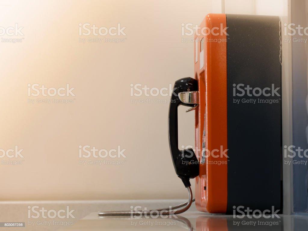Side view of orange public phone box. stock photo