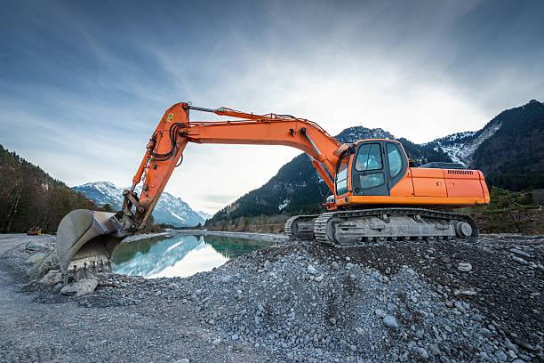Seitenansicht von orange Schaufel digger auf Kies am lake – Foto