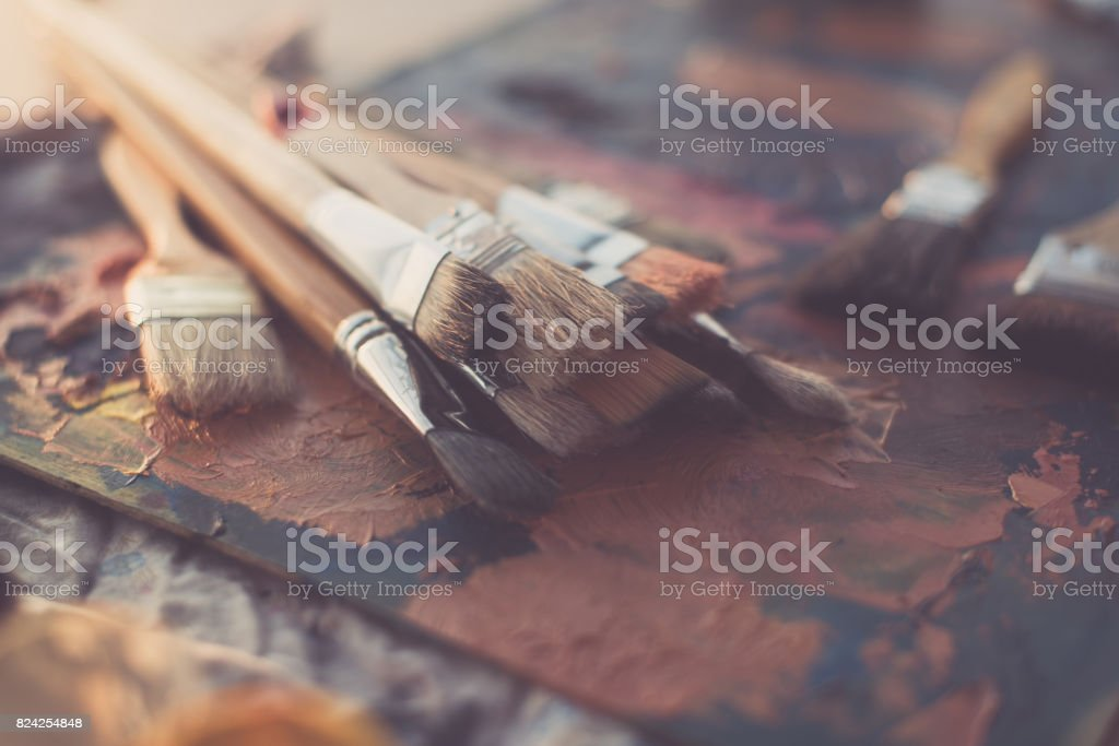 Side view of pallet with oil paint brushstrokes under paintbrush set in an art studio. stock photo