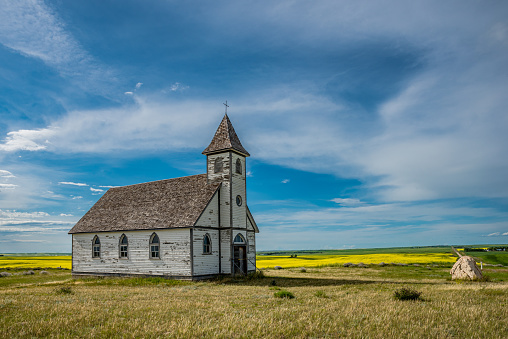 Side view of the historic, yet abandoned Peace Lutheran Church in Stonehenge, SK with a canola field and countryside in the background