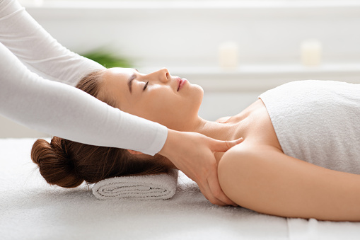 Side view of peaceful young lady having healing body massage from unrecognizable female therapist at modern newest spa. Spa attendant rubbing woman shoulders, stress relief concept