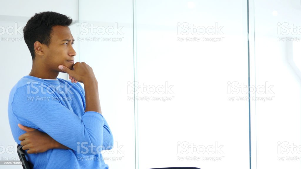 Side View of Pensive Afro-American Man Looking through Office Window