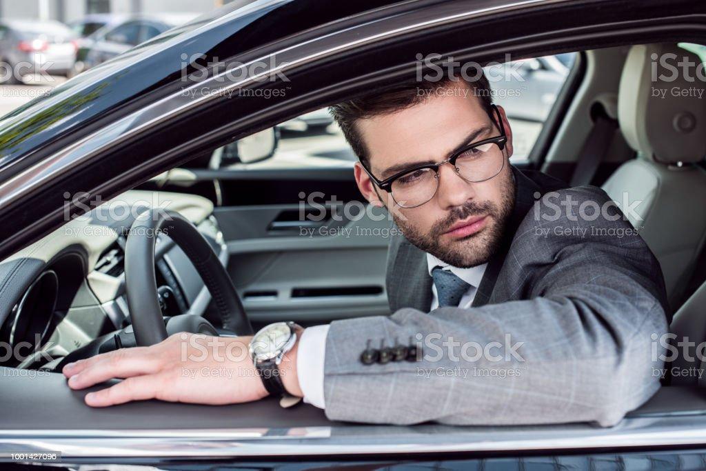 f0562b080e vista lateral del empresario pensativo en anteojos mirando lejos  conduciendo coche foto de stock libre de