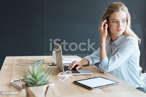 istock side view of pensive businesswoman looking away while sitting at workplace with laptop 823348890