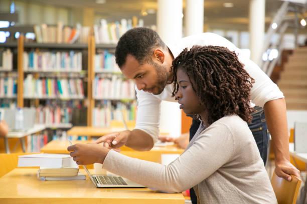 Seitenansicht von Personen, die in der Bibliothek sprechen und auf Laptop schauen – Foto