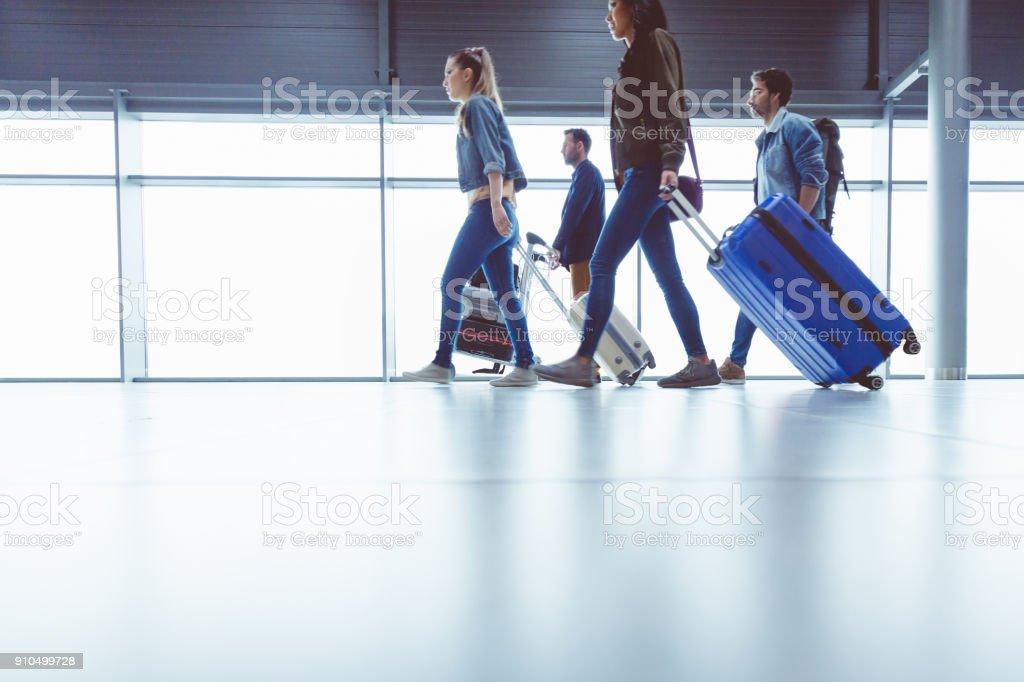 Seitenansicht des Menschen zu Fuß mit Koffer am Flughafen-terminal – Foto