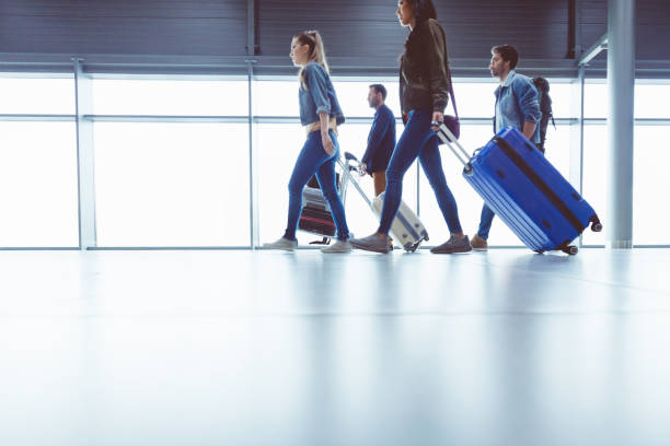 Side view of people walking with suitcase at airport terminal stock photo