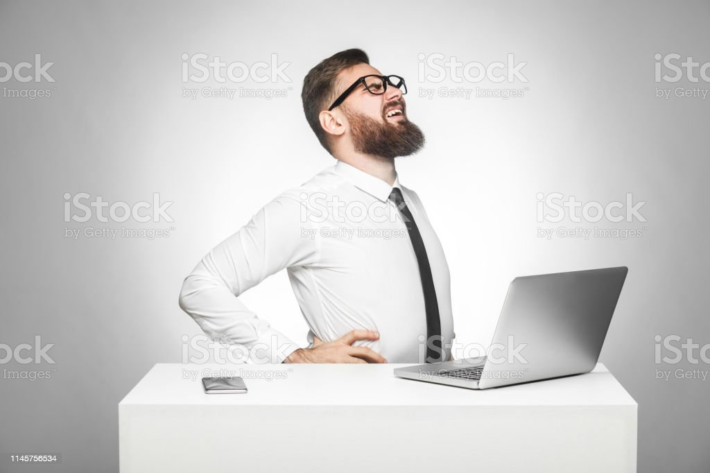 Side View Of Portrait Of Unhealphy Upset Young Manager In White Shirt And Black Tie Are Sitting In Office And Have Strong Backache Or Kidney Pain Stock Photo Download Image Now
