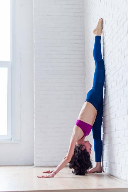 seitenansicht des professionellen athletin praktizieren yoga dehnen ihre waden, oberschenkel, oberschenkel tun stehen aufgeteilt übung - schlanke waden stock-fotos und bilder