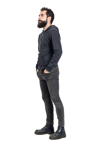 Side view of punker with hands in pockets looking up Side view of bearded punker or hipster with hands in pockets looking up. Full body length portrait isolated over white studio background. men in tight jeans stock pictures, royalty-free photos & images
