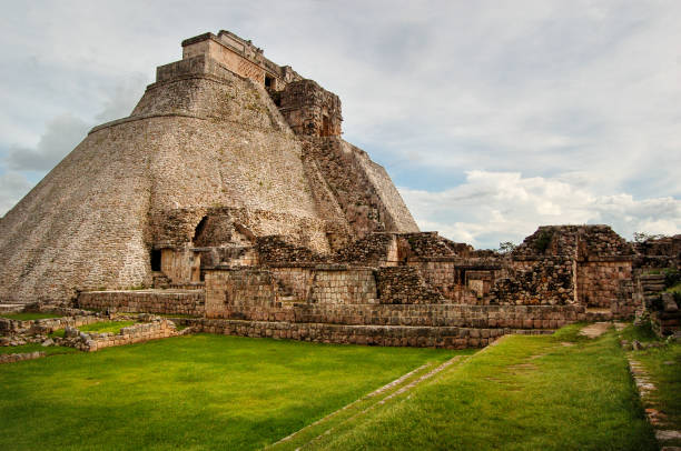 side view of pyramid of the magician ruins in uxmal on overcast day - uxmal stock photos and pictures