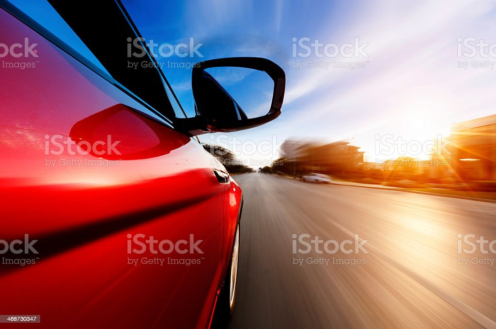 Side view of red car accelerating stock photo