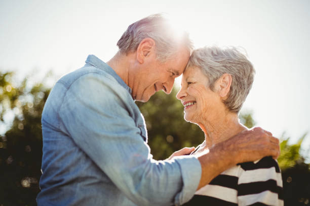 Side view of romantic senior couple looking at each other Side view of romantic senior couple looking at each other in back yard face to face stock pictures, royalty-free photos & images