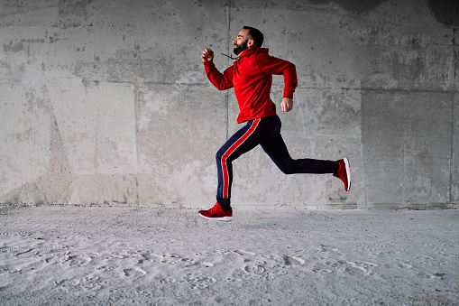 Side view of runner running fast under the bridge.