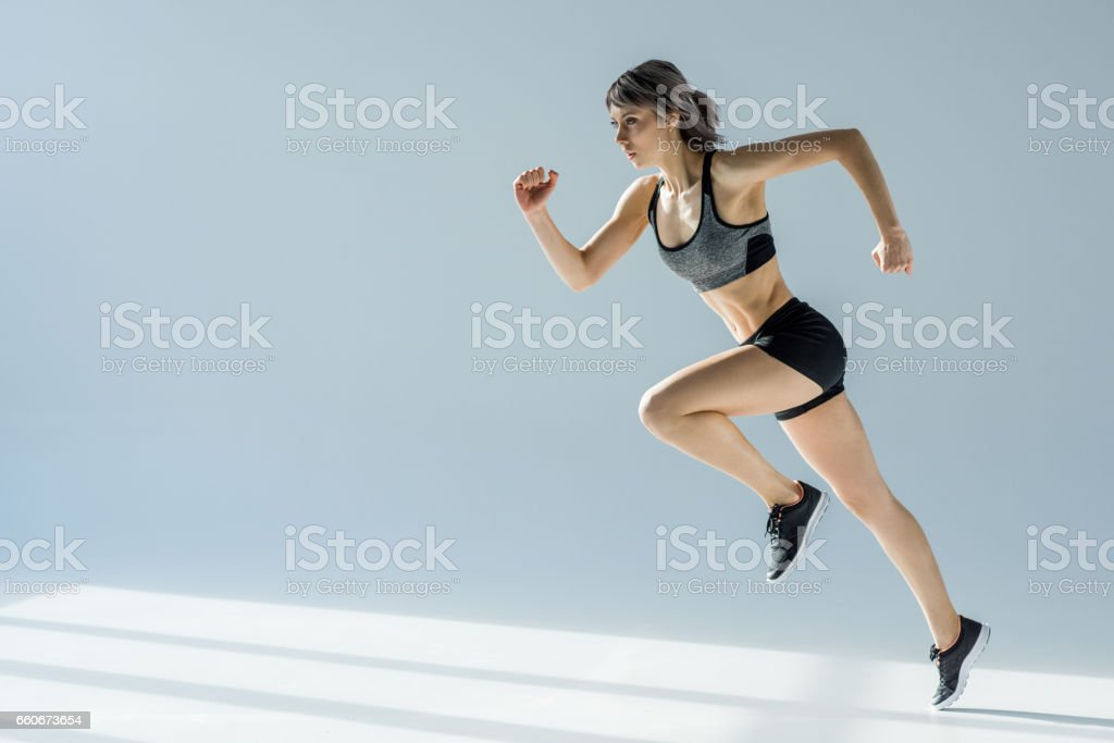 side view of running woman in sportive clothing on grey – zdjęcie