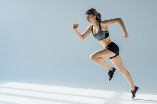 side view of running woman in sportive clothing on grey - carpet runner stock photos and pictures