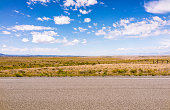 A horizon of rural land in Utah, USA, with the asphalt surface of the highway in the foreground.