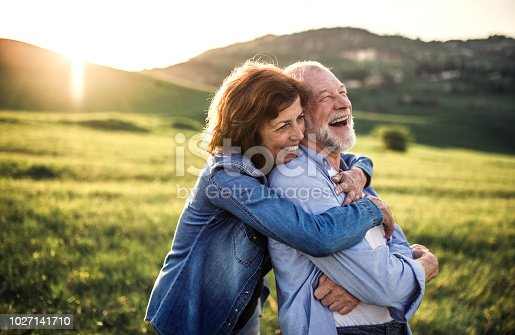 Happy senior couple outside in spring nature, hugging at sunset. Side view.