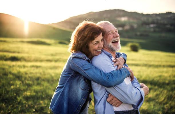 在日落時, 在春天的大自然中, 一對年長夫婦擁抱在外面。 - 幸福 個照片及圖片檔
