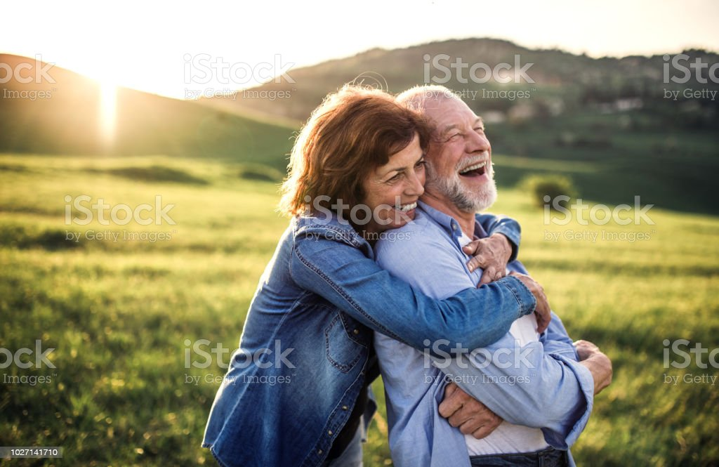 Side view of senior couple hugging outside in spring nature at sunset. stock photo