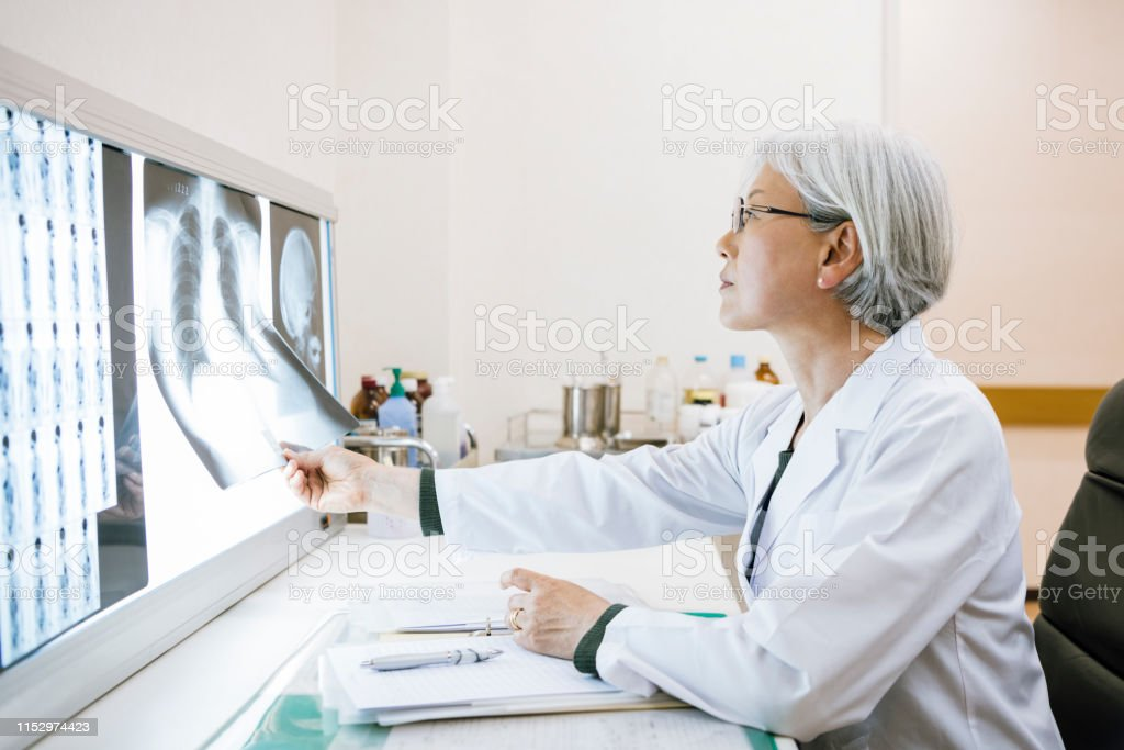 Seitenansicht der ranghohen Ärztin mit Blick auf Brust x Ray - Lizenzfrei 60-64 Jahre Stock-Foto