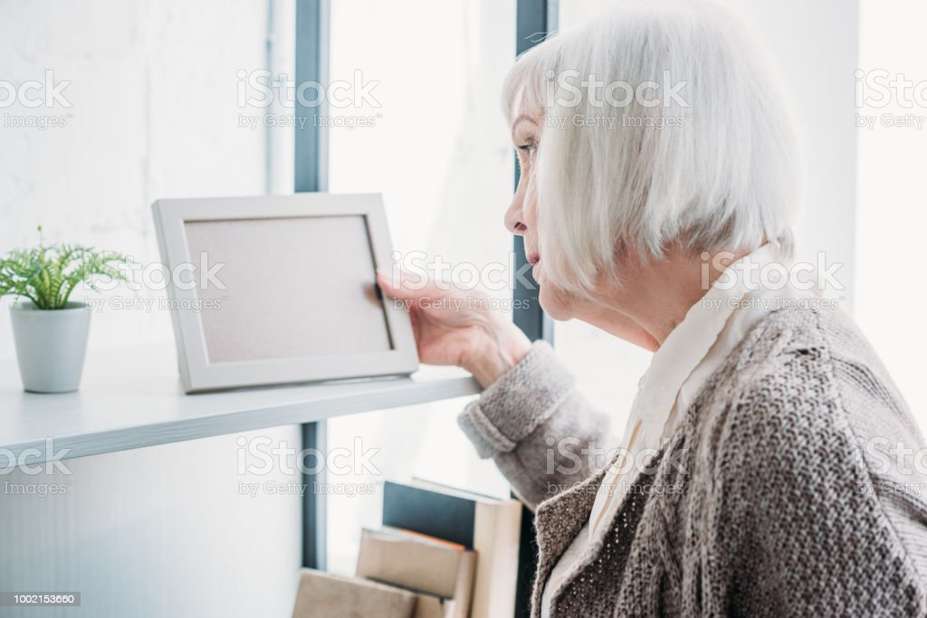 side view of senior lady looking at empty photo frame on bookshelf at home stock photo