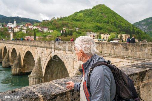 Side view of Senior man in front of The Bridge on the river Drina in Visegrad is famous bridge fron Nobel prize viner novel ( Na Drini čuprija) by Ivo Andric. Town of Visegrad is in background.
