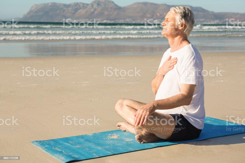老人在海灘冥想的側視圖 免版稅 stock photo