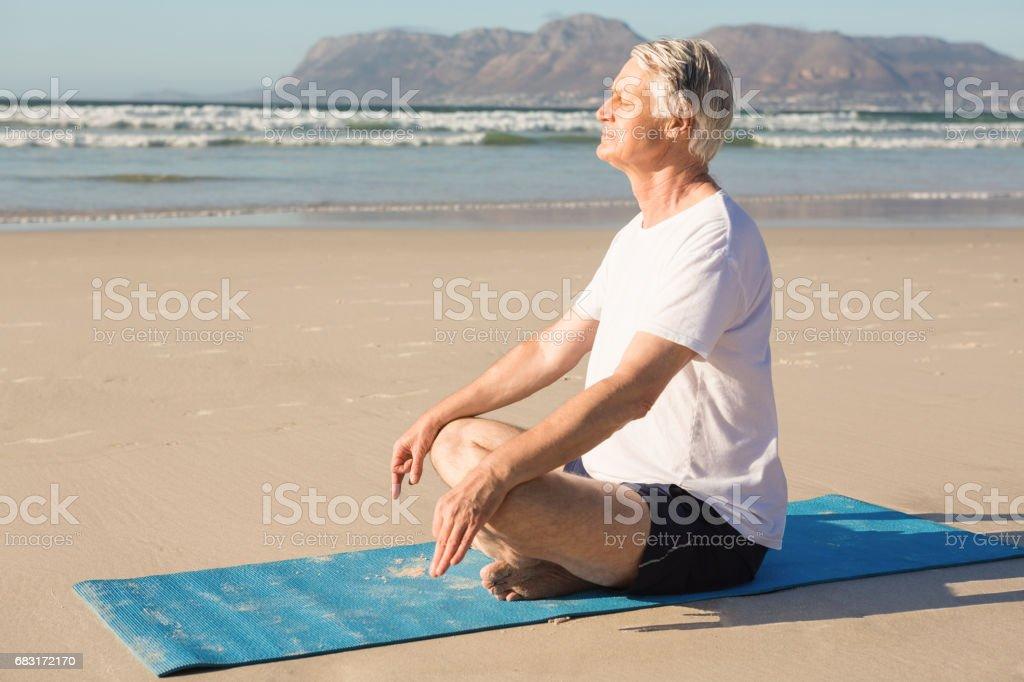 Side view of senior man meditating on mat at beach foto de stock royalty-free
