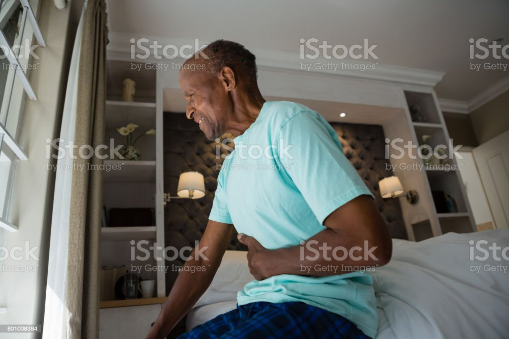 Side view of senior man suffering from stomachache at home stock photo