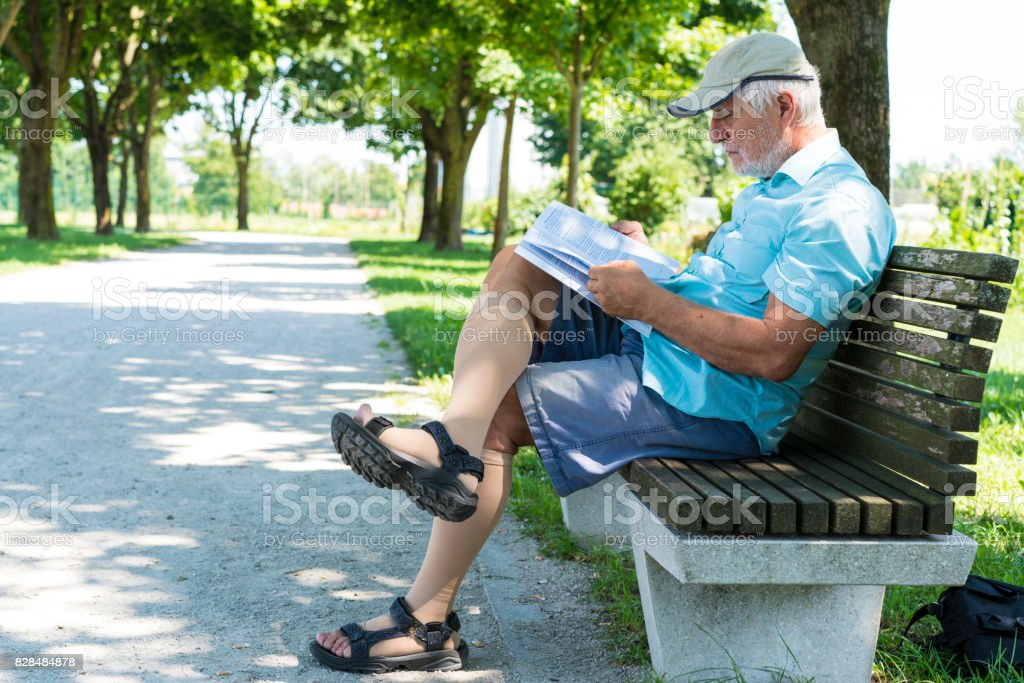 Side view of Senior reading a book while sitting on bench in shadow on The Trail of Remembrance and Comradeship in Ljubljana, Slovenia stock photo