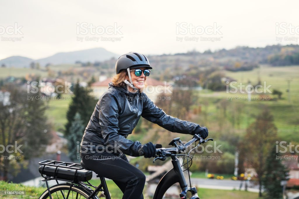 A side view of senior woman with electrobike cycling outdoors in countryside. stock photo