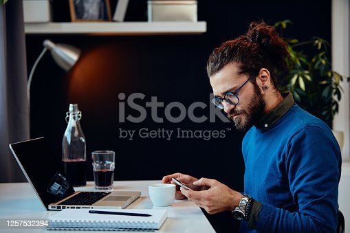 660311448 istock photo Side view of serious hipster sitting in his office and using smart phone. 1257532394