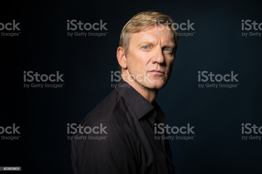 Side View Of Serious Man Against Black Background stock photo
