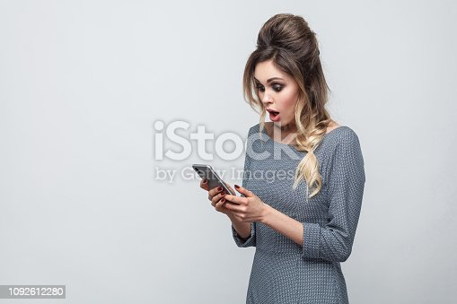 640046924 istock photo Side view of shocked beautiful blogger teenager wearing in grey dress with pigtail on head standing, using smartphone and watching video with amazed face. 1092612280