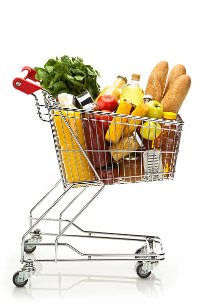 Side view of shopping cart filled with groceries and vegetables Side view of a metal shopping cart filled with a large variety of colorful groceries that includes some fresh vegetables, fruits, canned food, fruit juice, cooking oil and three loafs of bread. The cart is standing on reflective white background producing a soft reflection under it. The cart has a red plastic handle. DSRL studio shot with Canon EOS 5D Mk II   cart stock pictures, royalty-free photos & images