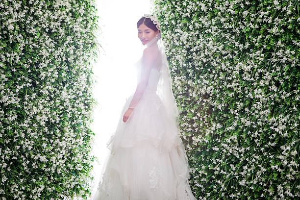 Side view of shy bride standing amidst flower decorations Side view of shy bride standing amidst flower decorations amidst stock pictures, royalty-free photos & images