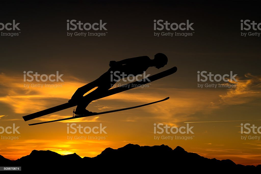 Side View of Ski Jumper in Mid-air Against the Sunlight stock photo