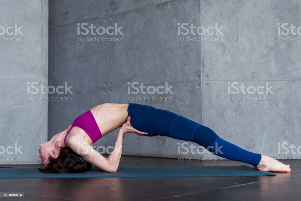 Side View Of Skinny Young Yogini Standing In Yoga Backbend Pose On Mat In Studio Stock Photo Download Image Now Istock