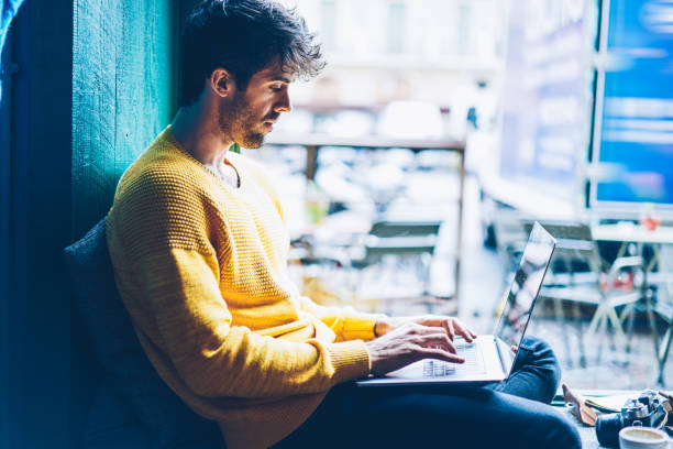 Side view of smart male copywriter typing on keyboard of modern laptop device working freelance in coworking space.Student in casual outfit searching information on website for coursework at netbook stock photo