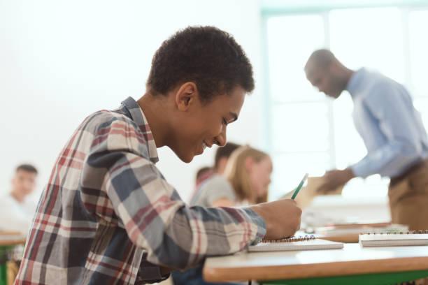 Seitenansicht des lächelnden afroamerikanischen jungen schriftlich Lehrbuch mit Lehrer und Mitschülern auf hinter – Foto
