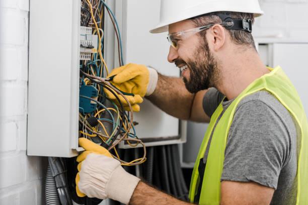 zijaanzicht van lachende knappe elektricien elektrakast repareren met een tang in gang - elektricien stockfoto's en -beelden