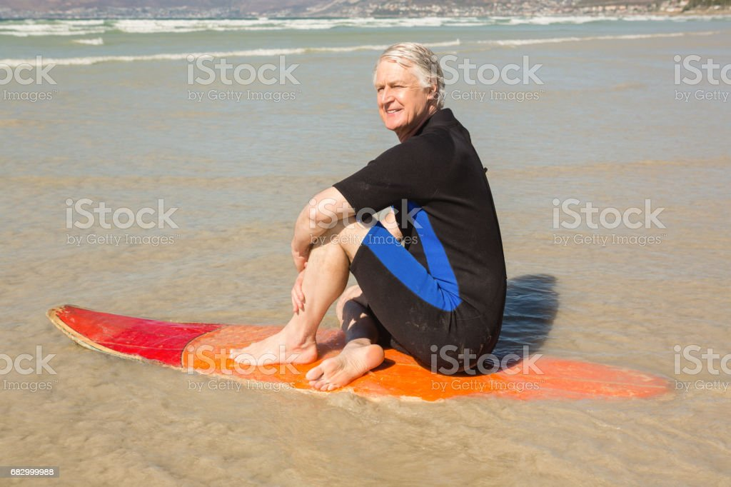 Side view of smiling senior man sitting on surfboard royalty-free stock photo